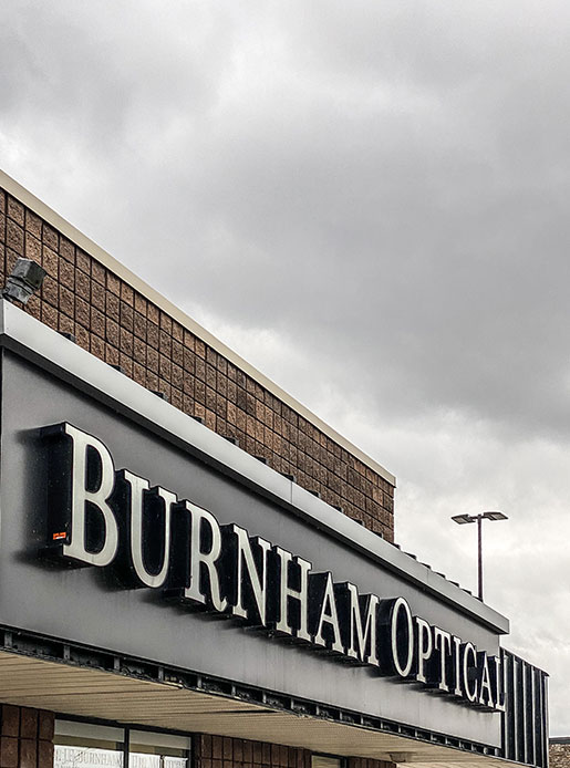 the storefront sign for burnham optical is shown in the bottom of frame