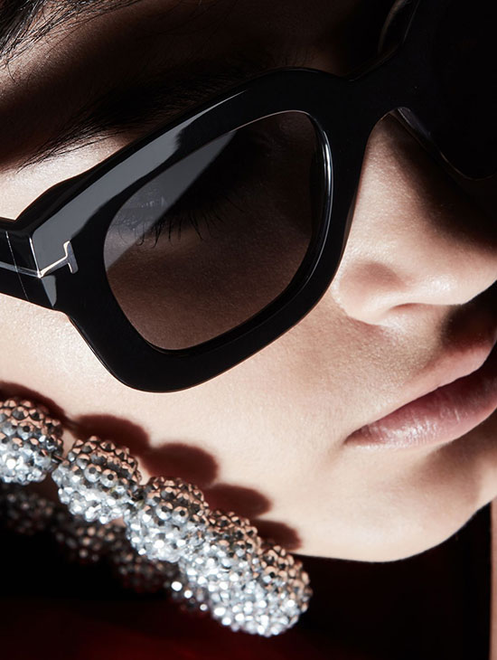 a close up shot of a woman's face who is wearing thick-rimmed tom ford sunglasses and a diamond earring.
